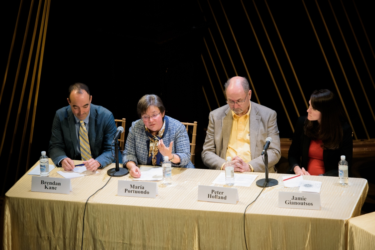 Four speakers sitting at a table with gold tablecloth on a stage