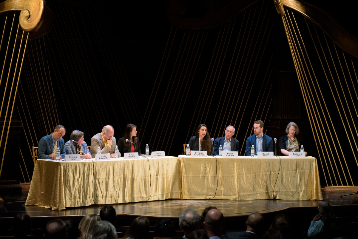 Eight speakers sitting at two tables with gold tablecloths on a stage