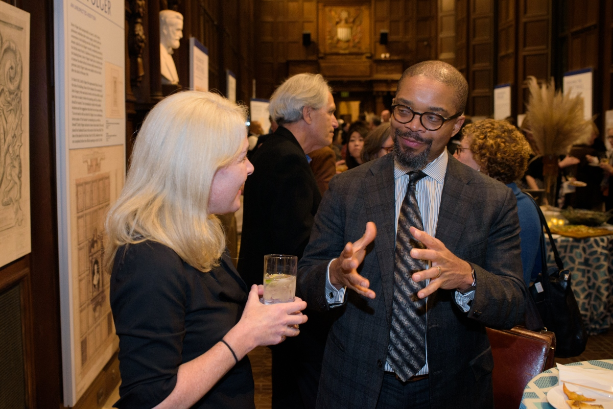 Two people standing and talking at the Folger Institute Roundtable reception