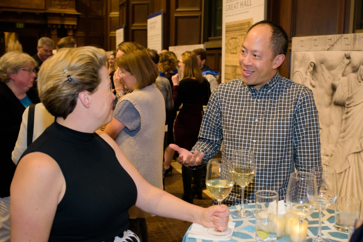 Two people standing at a cocktail table conversing