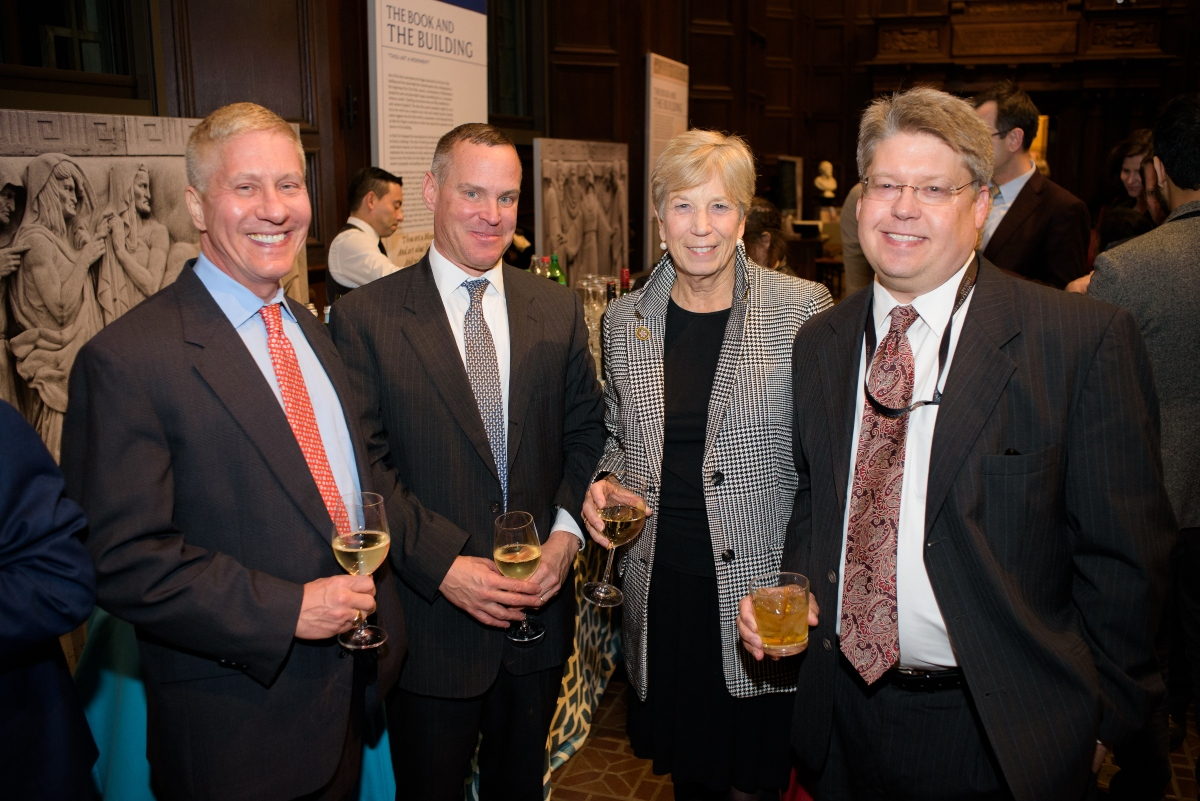 Four people standing and posing for a picture at the Folger Institute Roundtable Reception
