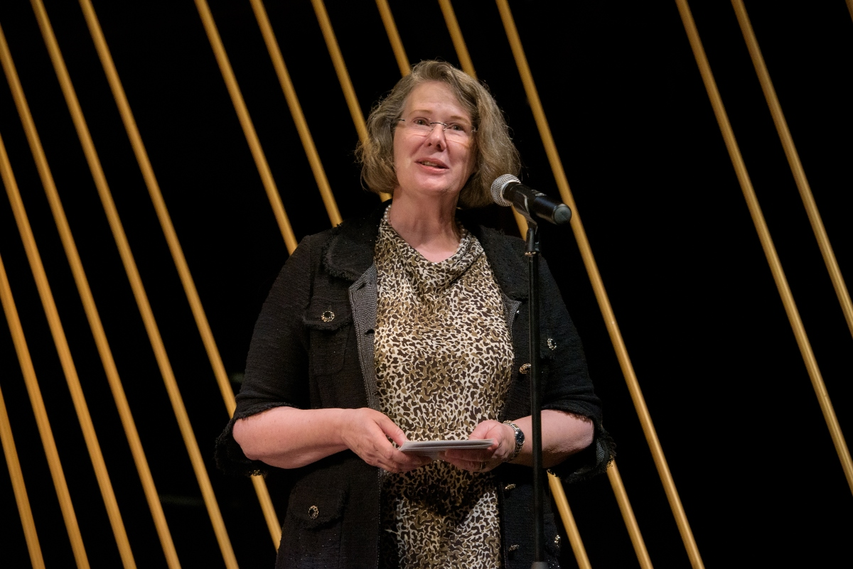 Folger Institute Executive Director Kathleen Lynch speaking into a microphone