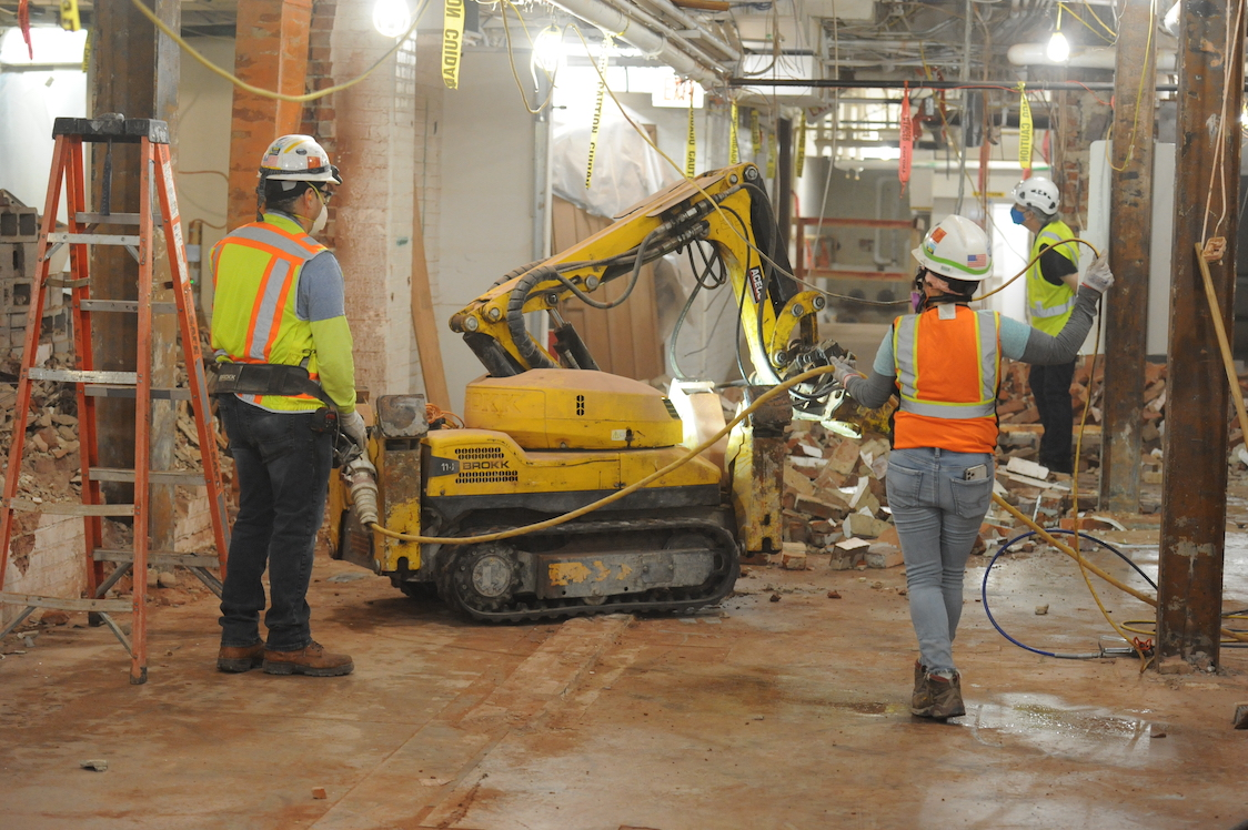 A three-person crew operates a remote-controlled jackhammer to break up a Deck A concrete floor to create new galleries at the Folger.