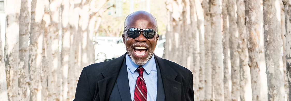 African-American Shakespeare Company Artistic Director L. Peter Callender, wearing a suit and sunglasses, laughs as he walks down an avenue of trees.