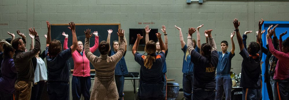 The Shakespeare in Prison Womens Ensemble in rehearsal. The women stand in a large circle onstage and raise their hands in the air together.