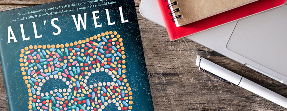 A copy of Alls Well, the novel by Mona Awad, lies on a desk with notebooks and pens.