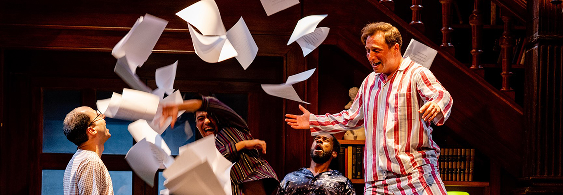 Actors Matt Dallal, Jack Schmitt, Joshua David Robinson, and Zachary Fine in Loves Labors Lost, Folger Theatre. Fine, as Berowne, stands on top of a desk in striped pajamas and joyously tosses a stack of paper into the air.