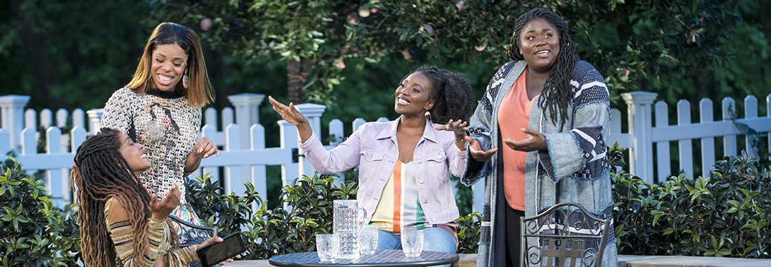 Tiffany Denise Hobbs, Margaret Odette, Olivia Washington, and Danielle Brooks gather around a table on a patio and laugh, in Much Ado About Nothing at the Public Theater's Shakespeare in the Park.