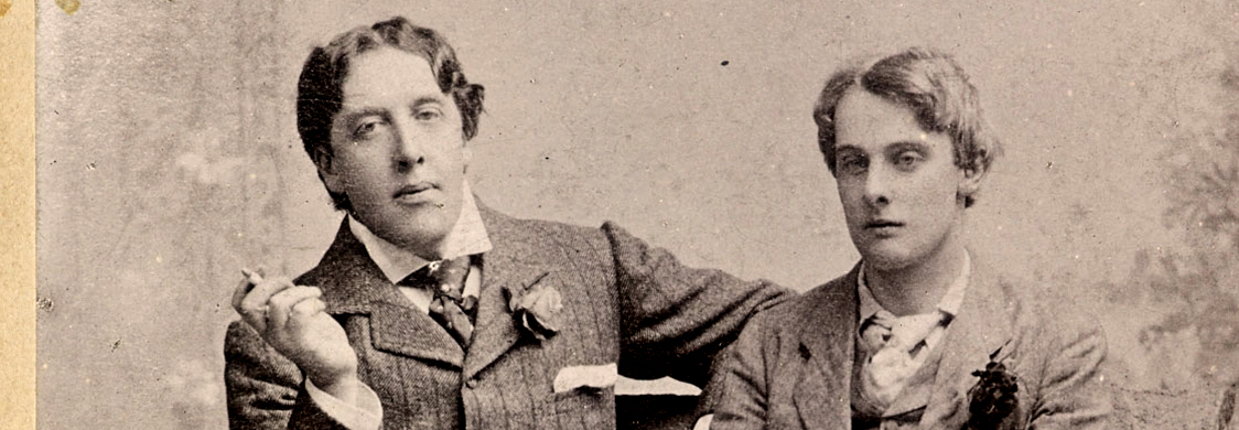 Oscar Wilde and Lord Alfred Douglass sit together on a bench.