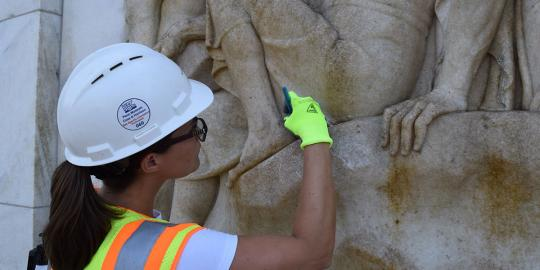 Woman cleaning a bas relief